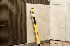 Carreaux de céramique sur une installation de mur Amélioration de l'habitat et renov photographie stock