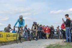 Two Cyclists - Paris Roubaix 2015. Carrefour de l`Arbre, France - April 12,2015: Daniil Fominykh of Team Astana and Jay Robert Thomson of MTN-Qhubeka Team Royalty Free Stock Image