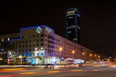 Carrefour de nuit avec le trafic et gratte-ciel à l'arrière-plan Image stock