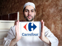 Carrefour logo. Logo of the international chain of convenience stores  carrefour on samsung tablet holded by arab muslim man Royalty Free Stock Photos