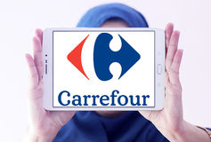 Carrefour logo. Logo of the international chain of convenience stores  carrefour on samsung tablet holded by arab muslim woman Stock Photography
