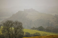 Carreg Cennen Castle in the Mist. Carreg Cennen Castle on a misty day with sheep in the fields below Royalty Free Stock Photo