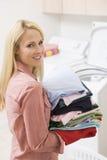 Carreg da mulher dobrado acima da lavanderia Fotos de Stock