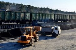 Carregador da roda que descarrega o carvão em um caminhão basculante pesado imagens de stock royalty free