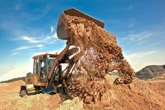 Carregador da roda que descarrega o solo no canteiro de obras imagem de stock