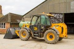 Carregador do escavador da construção na jarda de exploração agrícola com celeiro Fotografia de Stock