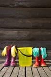 Carregadores de borracha, cubeta e luvas na varanda Fotos de Stock Royalty Free