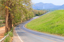 carreggiata per trasporto con la montagna e l'erba verde Fotografia Stock Libera da Diritti