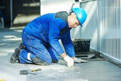 Carreleur à la rénovation de carrelage de plancher photographie stock