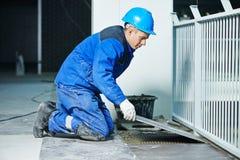 Carreleur à la rénovation industrielle de carrelage de plancher photographie stock