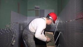 Carreleur professionnel ajoutant la colle de ciment sur la tuile avant d'installer le carreau de céramique banque de vidéos