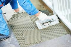 Carreleurs à la rénovation industrielle de carrelage de plancher photos stock