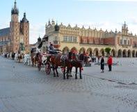 Carrelli del cavallo davanti alla chiesa di Mariacki sul quadrato principale di K Immagini Stock