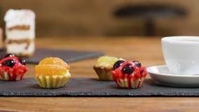 Carrello alto vicino sparato delle torte di frutta dolci e di una tazza di caffè video d archivio