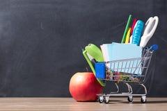 Carrello con i rifornimenti di scuola sopra il fondo della lavagna Immagini Stock Libere da Diritti