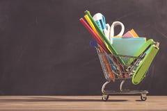Carrello con i rifornimenti di scuola sopra il fondo della lavagna Fotografia Stock Libera da Diritti