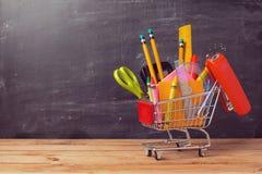 Carrello con i rifornimenti di scuola sopra il fondo della lavagna Di nuovo al concetto di vendita del banco Immagine Stock