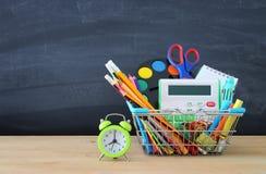 Carrello con il rifornimento di scuola davanti alla lavagna Di nuovo al concetto del banco fotografia stock libera da diritti