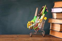 Carrello con il rifornimento ed i libri di scuola Immagini Stock Libere da Diritti