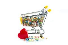 Carrello con le pillole, cuore di acquisto isolato su fondo bianco Immagini Stock