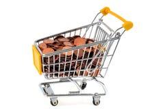 Carrello del supermercato riempito di monete su un fondo bianco fotografia stock libera da diritti