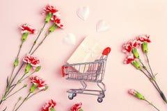 Carrello di acquisto con il contenitore di regalo, i cuori di amore e il flowe dei garofani Immagini Stock Libere da Diritti