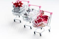 Carrello di acquisto con il regalo di natale Contenitore di regalo con il nastro rosso su un fondo bianco Decorazione di natale Immagine Stock