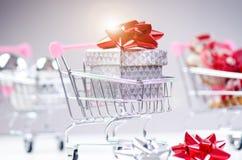 Carrello di acquisto con il regalo di natale Contenitore di regalo con il nastro rosso su un fondo bianco Decorazione di natale Immagini Stock Libere da Diritti