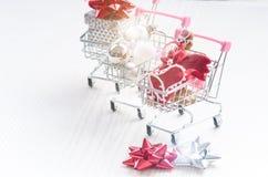 Carrello di acquisto con il regalo di natale Contenitore di regalo con il nastro rosso su un fondo bianco Decorazione di natale Fotografie Stock Libere da Diritti