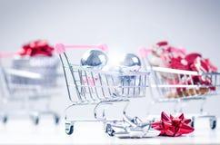 Carrello di acquisto con il regalo di natale Contenitore di regalo con il nastro rosso su un fondo bianco Decorazione di natale Fotografia Stock