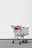 Carrello di acquisto con la priorità bassa della parete in bianco Fotografia Stock