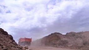 Carrello di miniera nella cava di calcare scena Chiuda su di due autocarri con cassone ribaltabile arancio che guidano dalla cima archivi video