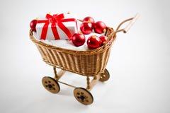 Carrello di natale con le bagattelle ed il regalo rossi della Santa Fotografia Stock