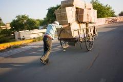 Carrello di trasporto delle caselle dell'uomo indiano a disposizione Immagine Stock