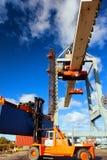 Carrello elevatore e gru arancio a caricamento ed allo scarico del carico nella t Fotografie Stock Libere da Diritti