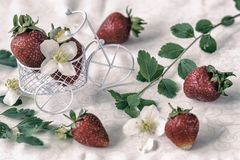 Carrello miniatura del giocattolo, carrello con le fragole mature, bacche, fiori, fondo d'annata Concetto di agricoltura Immagini Stock