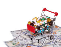 Carrello in pieno con le pillole sopra le banconote in dollari, isolate Fotografie Stock