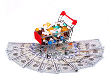 Carrello in pieno con le pillole sopra le banconote in dollari, isolate Fotografia Stock Libera da Diritti
