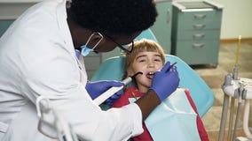 Carrello sparato del dentista maschio africano che tratta i denti della bambina archivi video