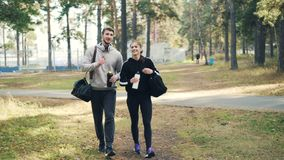 Carrello sparato della ragazza felice e del tipo che camminano insieme in abiti sportivi d'uso del parco della città e che tengon stock footage