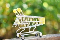 Carrello sul concetto di compera online di Black Friday del fondo del bokeh di verde della natura con il carrello giallo fotografia stock