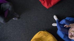 Carrello superiore preso dell'uomo e della donna che giocano con la palla che si siede sulle borse molli multicoloured video d archivio