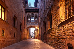 Carrer del Bisbe in Gothic Quarter, Barcelona. Narrow cobbled medieval Carrer del Bisbe street with Bridge of Sighs in Barri Gothic Quarter in the morning stock image