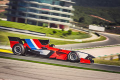 Carreras de coches rápidas de la fórmula en una pista Fotos de archivo