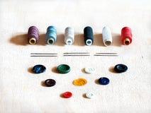 Carretéis com linha, as agulhas e os botões coloridos Imagens de Stock Royalty Free