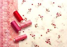 Carretéis cor-de-rosa da linha em uma tela floral Fotografia de Stock