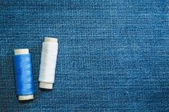 Carretéis da linha branca e azul do algodão na tela das calças de brim com espaço da cópia foto de stock