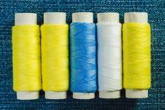 Carretéis da linha costurando branca, amarela e verde arranjada na fileira na sarja de Nimes imagem de stock
