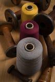 Carretéis da linha da cor alinhados verticalmente com os carretéis de madeira Imagem de Stock