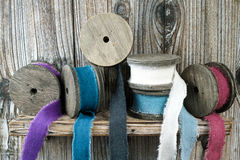 Carretéis de madeira coloridos com as fitas de linho no fundo de madeira Imagens de Stock Royalty Free